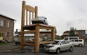 A car sits on a giant wooden chair -RNPS IMAGES OF THE YEAR 2008 A car sits on a giant wooden chair in front of a furniture factory in the city of Abakan in the Siberian Khakassia region, 408 km (253.5 miles) to the south of Russia's Siberian city of Krasnoyarsk,-